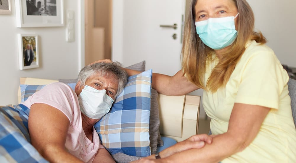 caregiver helping elderly mother with masks on